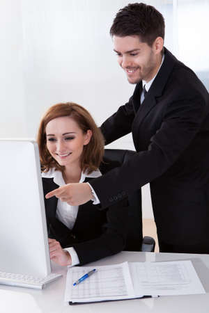 Two happy business partners looking at computer photo