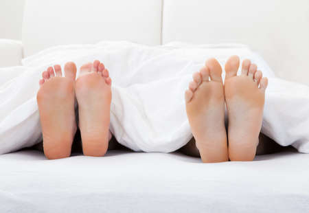 adult's feet: Close-up of couples feet sleeping on bed in bedroom