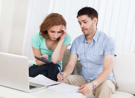 Portrait of young worried couple calculating budget photo