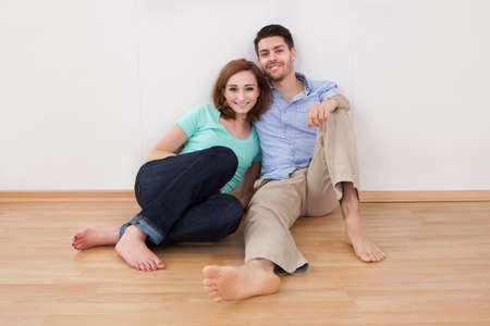 barefoot man: Portrait of happy young couple sitting on hardwood floor