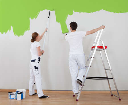 Portrait Of Young Couple Painting Wall Together Stok Fotoğraf