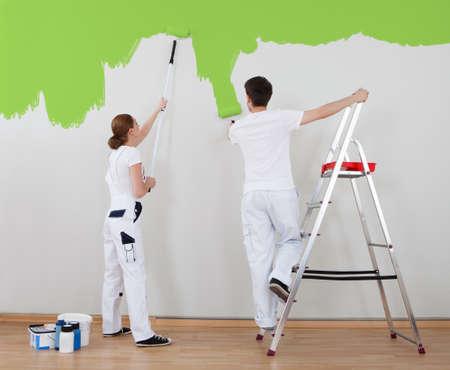 hombre pintando: Retrato de joven pareja pintura muro junto