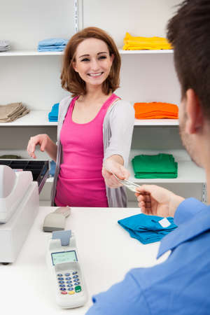 Client Handing Over Credit Card To A Happy Female Cashier photo