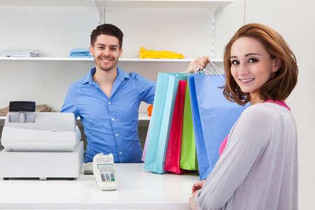 tezgâhtar: Müşteri için Alışveriş Çantası fazla mutlu Erkek Kasiyer Handing Stok Fotoğraf