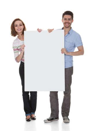 Joven pareja feliz celebración Cartel sobre el fondo blanco