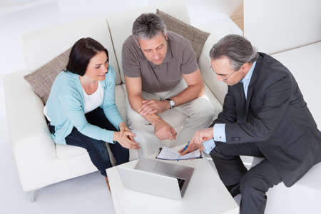 financial advice: Happy Couple And Mature Consultant Discussing Together Stock Photo