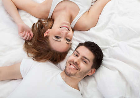 Portrait of happy young couple lying on bed together photo