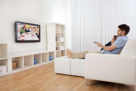 tv: Jeune couple assis sur le canapé à regarder la télévision
