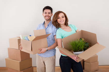 Young Happy Couple Holding Moving Into New House photo