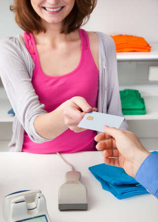 Client Handing Over Credit Card To A Happy Female Cashier