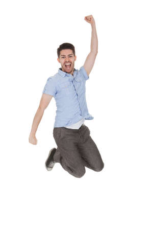 Young Man Jumping With Arms Raised Over White Background photo