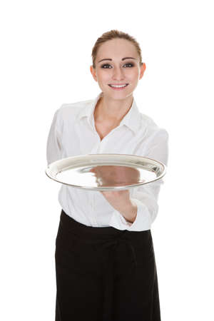 Happy Young Waitress Holding Tray Over White Background photo