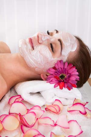 body skin: Beautiful young woman getting facial mask at spa studio