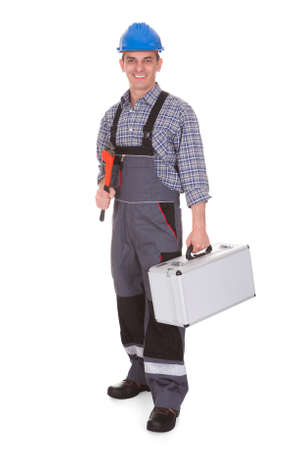 Worktool 白い背景の上に保持している幸せな男性労働者