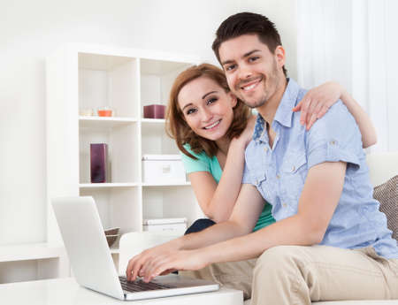 Portrait of young happy couple using laptop photo