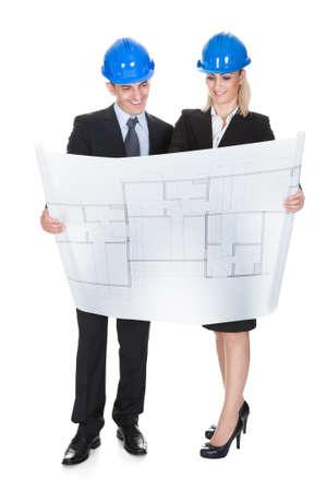 ingeniero civil: Arquitectos masculinos y femeninos que miran el modelo sobre el fondo blanco