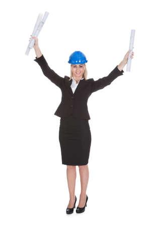 Portrait Of Excited Female Architect Holding Blueprint Over White Background Stock Photo - 20789400