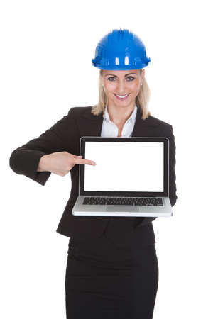 Portrait Of Happy Female Architect Holding Laptop Over White Background photo