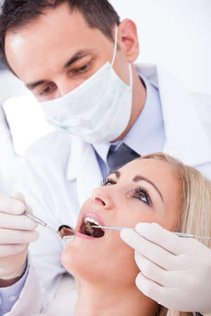 cavity braces: Male Dentist Examining Female Patient In Clinic