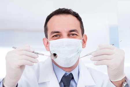 carver: Portrait Of Male Dentist Holding Angled Mirror And Carver Stock Photo
