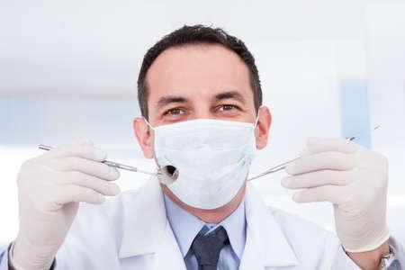schnitzer: Portrait von m�nnlichen Zahnarzt mit Zahnspiegel und Carver