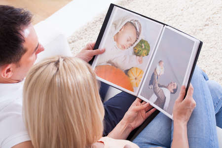 photo album book: Portrait Of Couple Looking At Photo Album
