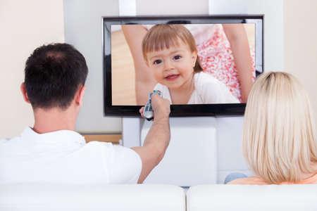 personas viendo tv: Retrato de la pareja sentada en el sof� viendo la televisi�n