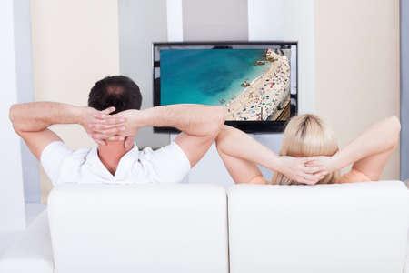 pareja viendo tv: Retrato de la pareja sentada en el sof� viendo la televisi�n