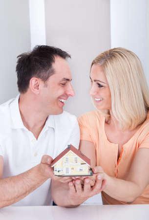 Portrait of happy couple holding house model photo