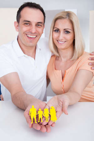 Portrait of happy couple holding family figure cut-out photo