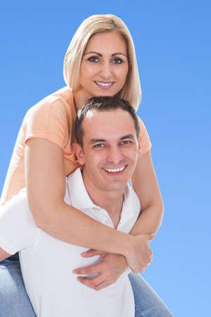 piggy back: Happy Man Piggybacking His Girlfriend Against Blue Sky