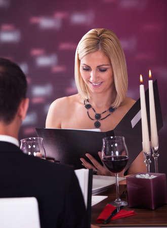 donne eleganti: Coppia seduta al ristorante Donna scegliendo il menu Archivio Fotografico