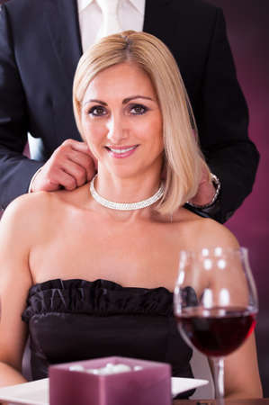 Happy Man Wearing Necklace To Girlfriend In Elegant Restaurant photo