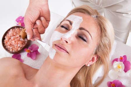 ansikts: Kosmetiker Tillämpa Facial Mask i ansiktet av unga vackra kvinnan I Spa Salon