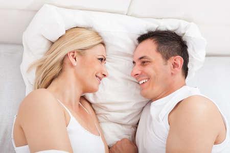 jovenes enamorados: Retrato de los amantes que se abrazan en la cama Foto de archivo