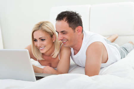 Happy Couple In The Bedroom Using Laptop photo