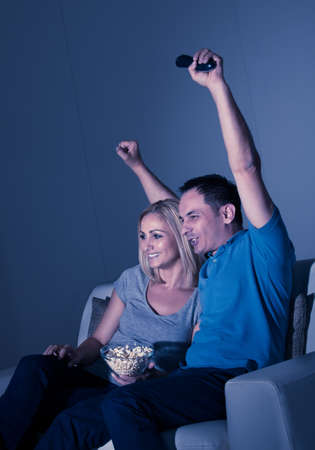 Excited Couple Watching Television And Eating Popcorn photo