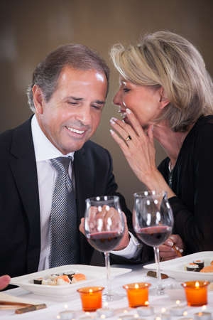 Cheerful Woman Whispering Something In Mans Ear In A Elegant Restaurant photo