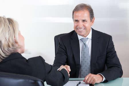 成熟した女性実業家およびオフィスでビジネスマンの握手