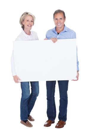 mature adult men: Coppie mature felici che tiene cartello vuoto isolato su sfondo bianco Archivio Fotografico