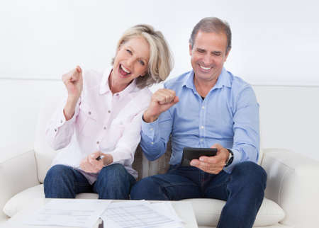 counting money: Portrait Of A Couple Sitting On Couch Enjoying Success