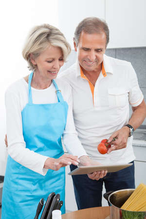 Mature Man And Woman Cutting Vegetable In Kitchen photo