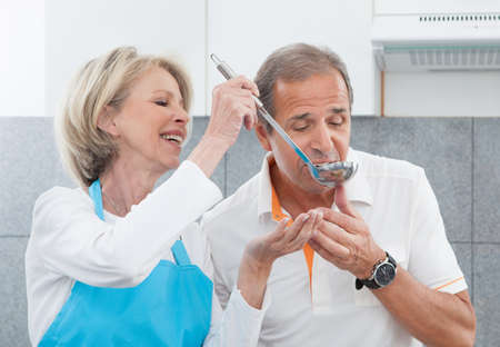 food testing: Woman Making His Husband To Taste The Food In Kitchen Stock Photo