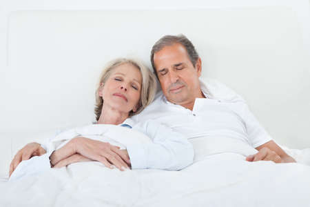 involved: Portrait Of Happy Senior Couple Sleeping Together In Bed
