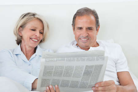 Portrait Of Mature Couple Reading Newspaper Together At Home photo