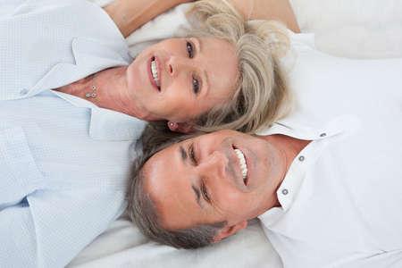 couple au lit: Portrait Of Happy Senior Couple couch� sur le lit Banque d'images