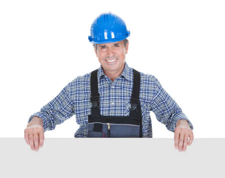 Happy Worker Over White Background Pointing Finger On Placard photo