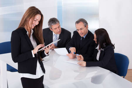 executive meeting: Happy Businesswoman Using Digital Tablet In Front Of Her Colleagues