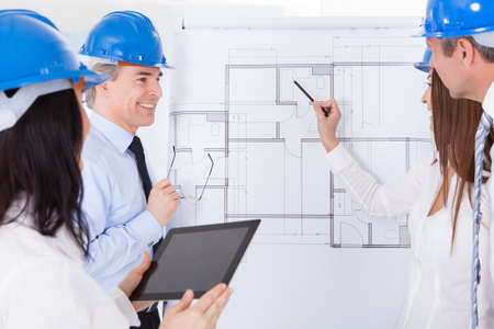 Group Of Architects Discussing New Project On Whiteboard photo