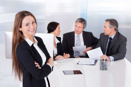Happy Businesswoman In Front Of Her Colleagues photo